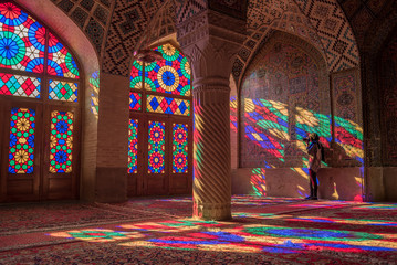 Unidentified woman traveler photograph the colorful light through stained glass window inside Nasir Al-Mulk (Pink Mosque), a traditional mosque in Shiraz, Iran.