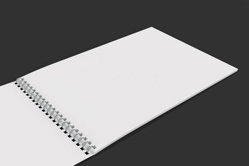 Open blank white notebook with metal spiral bound on black background