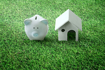 Piggy bank and house design on grass Ideas to save money on buying real estate or new loans for planned investments in future ideas.