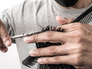 Attractive barber with dark hair doing a haircut for client with scissors isolated on white background.