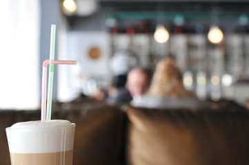 A cup of coffee stands on a brown table in a cafe. A cup of beautiful and fragrant latte with a slice of sugar - a refined sugar and tubules is on the table in a cafe. Cafe inside with visitors and la