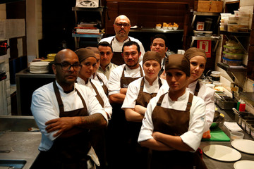 Chef Carlos Garcia and his crew, pose for a picture within the kitchen of the Alto restaurant in Caracas