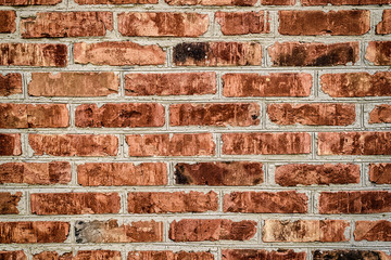 Grunge red brick wall background with copy space, texture pattern. Old texture of red stone blocks closeup, free space