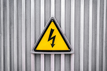 High voltage yellow triangle warning sign on gray metal wall. Danger electricity warning sign. Black lightning arrow symbol on yellow background in triangle
