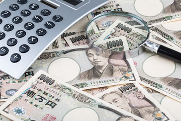 Stack of Japanese currency yen or Japanese banknotes and Japanese yen coins with magnifying glass and calculator