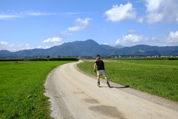 Man rollerblading on rural road, Slovenia