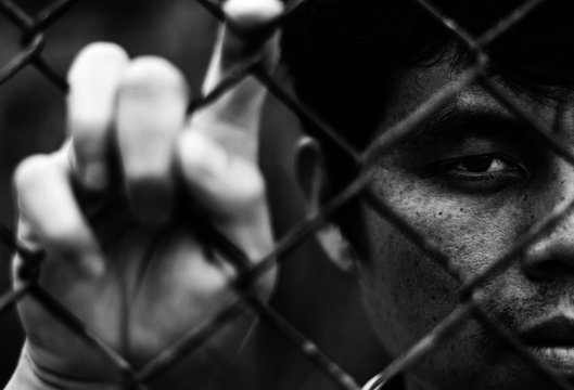 Depressed man standing behind a fence, hand grabs steel mesh cage