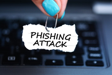 Phishing attack threat with woman hand holding fishing hook against laptop keyboard