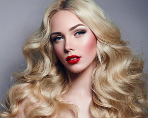 Beautiful young girl with luxurious light wavy hair close-up in the studio. Blonde - shiny, light long hair, curls. Makeup - arrows, red lipstick, pink blush. Cosmetics, hair care.