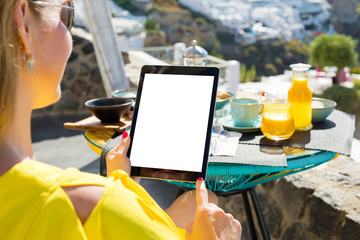 Woman using ipad while having breakfast, vertical screen orientation