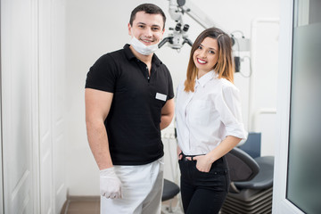 Portrait of friendly male dentist with happy female patient in modern dental clinic. Doctor and patient smiling and looking to the camera. Dentistry