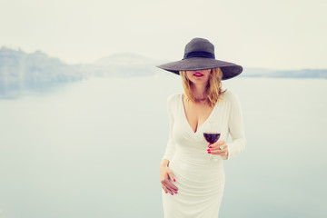 Woman enjoying glass of wine. Retro, vintage style filter.