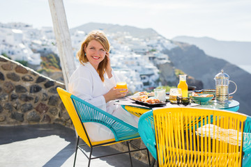 Woman in bathrobe having breakfast on terrace