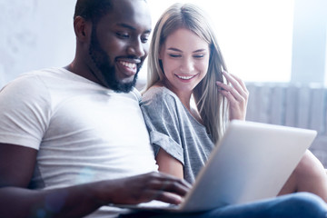 Peaceful young international couple using gadget at home