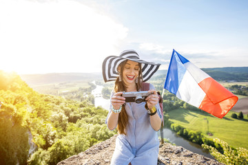 Young happy woman tourist with photo camera and french flag traveling near the Domme village in France