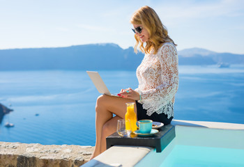 Business woman using laptop by the pool