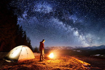 Male hiker have a rest in his camp near the forest at night. Man standing near campfire and tent under beautiful night sky full of stars and milky way. Long exposure Fototapete
