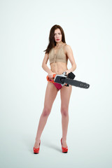 Young girl in bikini holding electric saw on background. Woman with tools concept