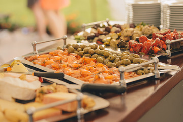 plate with appetizer : artichokes, smoked salmon, peppers, olives , catering