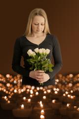 Trauernde Frau steht mit Blumen vor einem Kerzenmeer