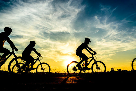 Silhouette of cyclist riding on  bike at sunset.
