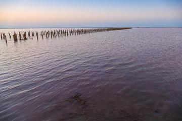 Landscape of lake at sunrise / Abandoned destroyed wooden pier on lake at dawn