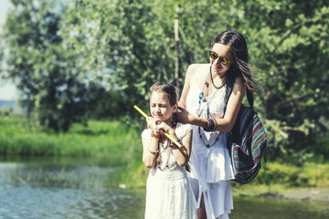 Beautiful and happy young mother and little daughter on nature bright Sunny day together