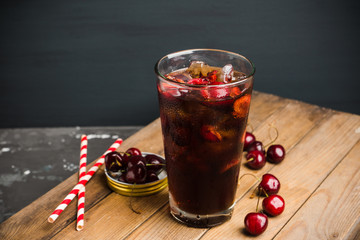 Refreshing cold cherry cola on the wooden background