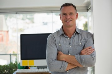 Portrait of smiling confident businessman standing at studio