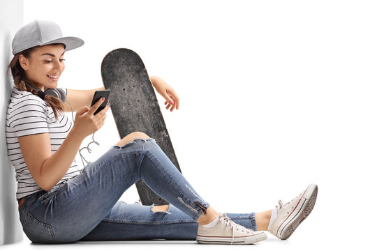 Teenage girl with a skateboard looking at a phone