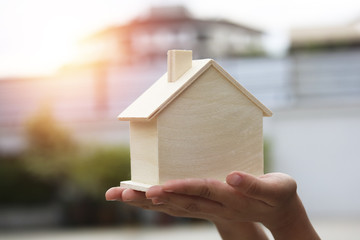 Mortgage concept, hand present and show wood house and ready to serve, concept as buying, saving, selling, finance,account and investment for home and condominuim