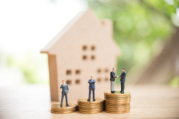 Miniature people,Real estate investment. House and coins on table.