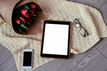Top view smartphone or mobile phone with copy space, hipster style, glasses and red tulips in a kraft paper