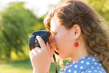 Closeup side profile view of young woman taking a picture looking through camera outdoors in green park and river