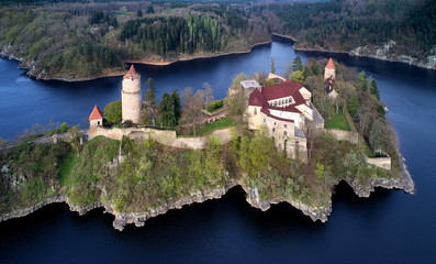 Aerial view on czech medieval secular castle Zvikov, situated on rocky outcrop above the confluence of two rivers in the centre of beautiful, spring nature. Castle between two rivers. Czech landscape.