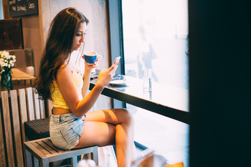 Young millennial woman using phone in coffee shop