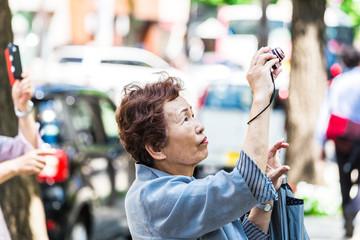 カメラで撮影している高齢者女性