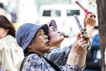 携帯電話のカメラで撮影している高齢者女性