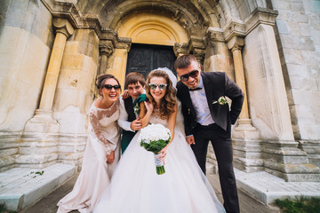 Full length portrait of newlywed couple dancing and having fun with bridesmaids and groomsmen in the city. Boys and girls in glasses.