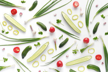 Fototapete - Abstract composition of vegetables. Vegetable pattern. Food background. Top view. Large and small cucumbers, garlic, tomatoes and green onions on a white background. Food concept. Sliced vegetables.