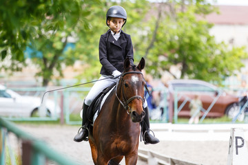 Young teenage girl in helmet riding horse on dressage equestrian competition