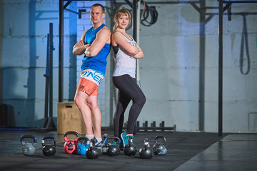 Sporty man and young muscular woman doing an exercise with weights in the gym