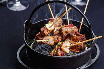 Meat on skewers smoks in a brazier with onion