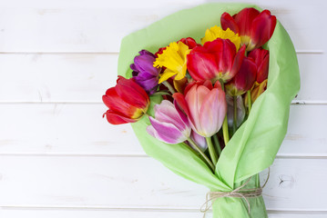 bouquet of colorful tulips wrapped in paper on  a wooden  background