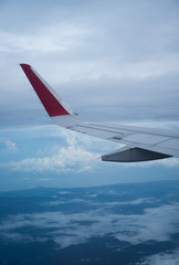 View through the aircraft window of wing over clouds and sky background