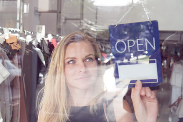 Pretty blond woman turning the open and closed sign in clothes shop