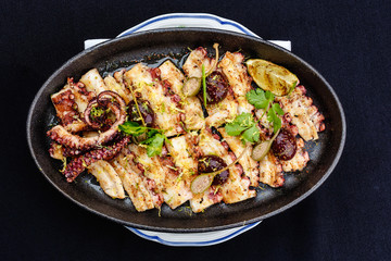 Fried octopus on a brazier seasoned with herbs and lemon. Pan asian cuizine