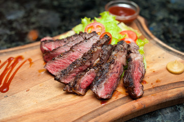 Juicy sliced steak from marbled beef on a wooden board