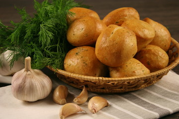 Homemade buns with garlic and dill on wooden table