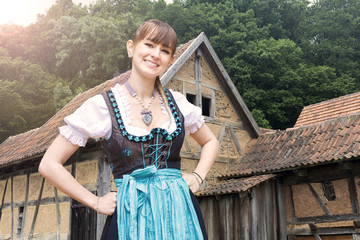 young woman in dirndl in front of old farm houses